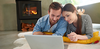 Couple huddled in front of fire