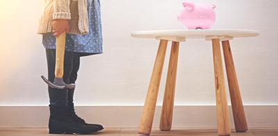 Little girl breaking piggy bank